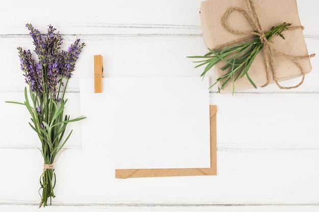 Ramo de flores de lavanda; papel blanco y caja presente envuelta en la mesa de madera Foto gratis