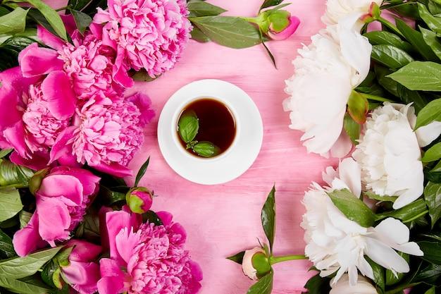 Ramo de flores de peonía y taza de café Foto Premium