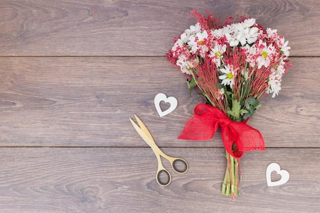 Ramo de flores con pequeños corazones en mesa. Foto gratis