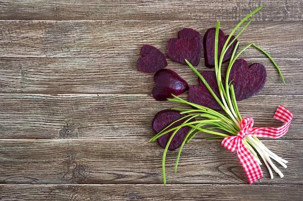 Un ramo de flores de rodajas de remolacha hervida y cebolla verde sobre un fondo de madera. amar la remolacha. concepto de alimentación saludable feliz día de san valentín. copia espacio Foto Premium