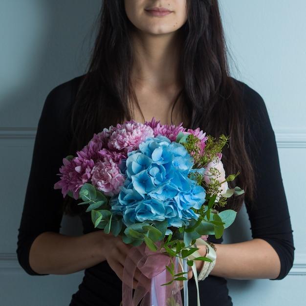 Ramo de flores de tonos rosados y azules en manos de una mujer Foto gratis