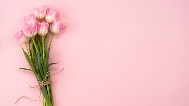 Ramo de flores de tulipán grande en mesa rosa Foto gratis