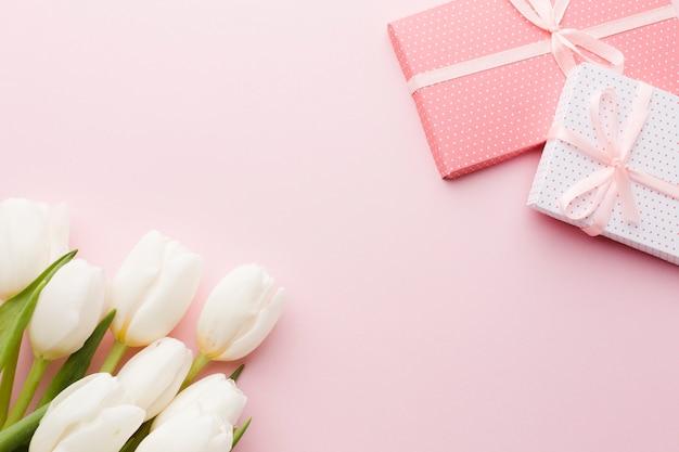 Ramo de flores de tulipán y regalos sobre fondo rosa Foto gratis