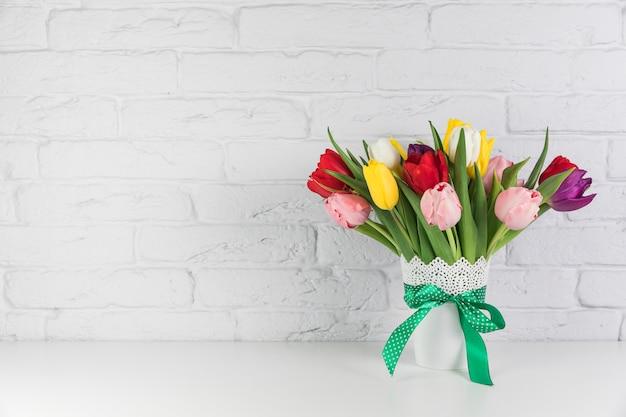 Ramo fresco hermoso colorido de los tulipanes en el escritorio contra la pared de ladrillo blanca Foto gratis
