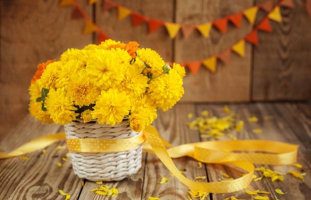El ramo hermoso de crisantemos amarillos florece en cesta de mimbre en el fondo de madera Foto Premium