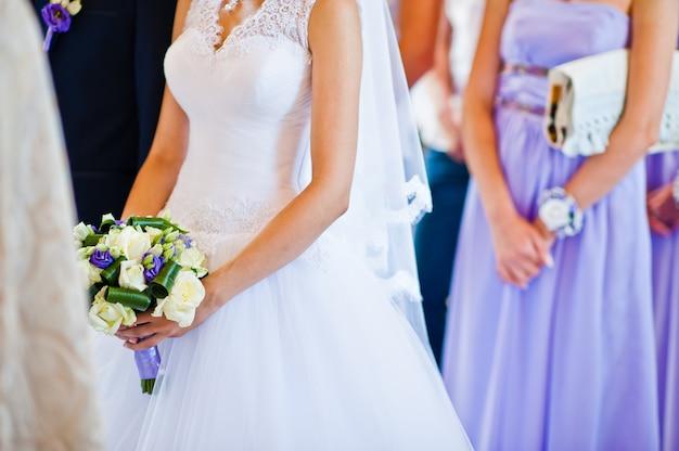 Ramo de novia violeta en la mano del fondo de la novia novio y dama de honor Foto Premium
