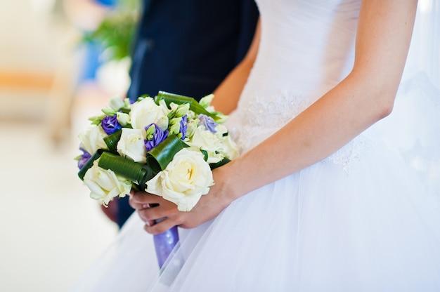 Ramo de novia violeta en mano del novio de fondo de novia Foto Premium