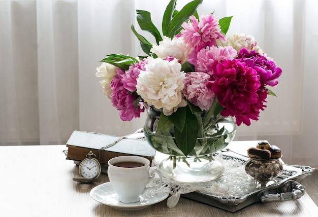 Un ramo de peonías multicolores, eclairs en un jarrón, una taza de té, un libro y un reloj de bolsillo. Foto Premium