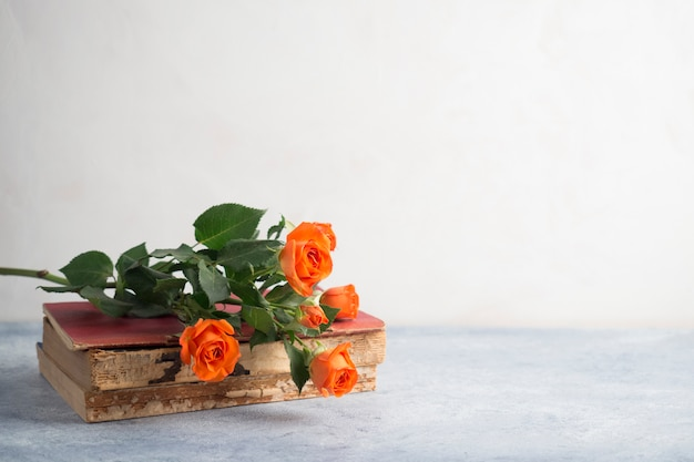 Ramo de rosas colocado en la pila de libros antiguos Foto gratis