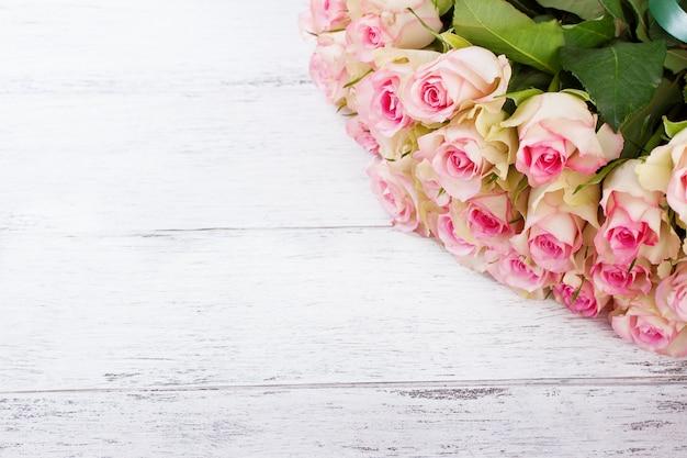 Ramo de rosas de color rosa con cinta azul sobre un fondo de madera de época Foto gratis