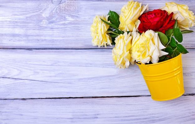 Ramo de rosas frescas en un cubo de hierro amarillo Foto Premium