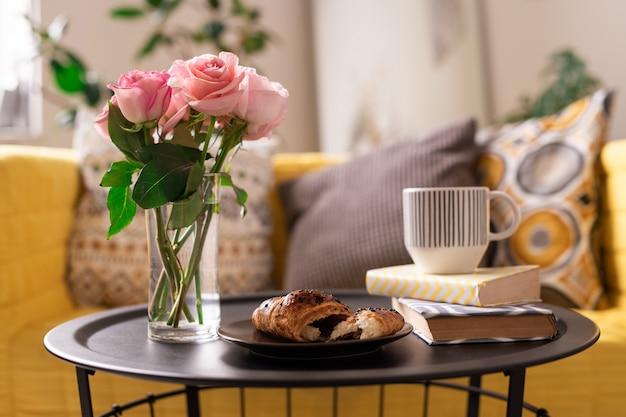 Ramo de rosas frescas en un vaso de agua, croissant casero, taza de té o café y dos libros en la bandeja Foto Premium