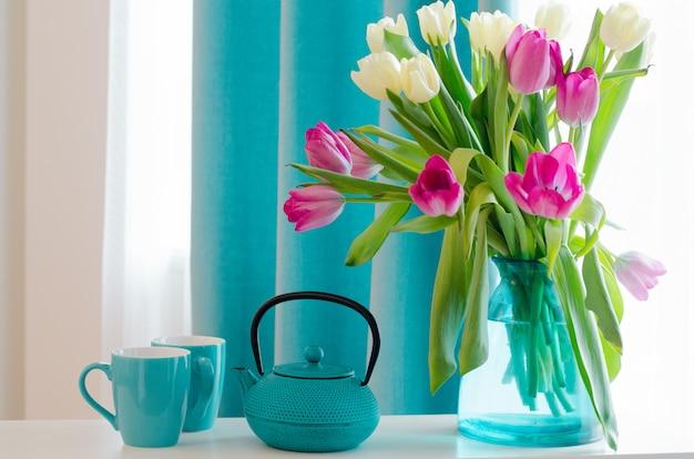 Ramo de rosas hermosas y tulipanes en jarrón tiffany, taza, platillo y tetera. Foto Premium
