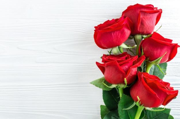 Ramo de rosas rojas sobre fondo blanco de madera. Foto Premium