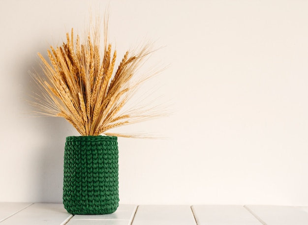 Ramo de trigo seco y centeno en un jarrón de punto verde sobre una pared blanca Foto Premium