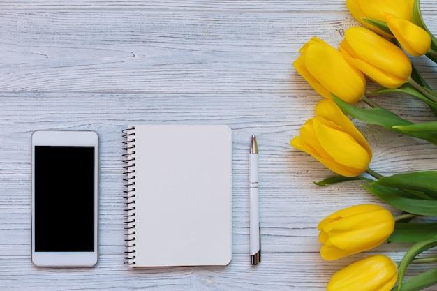 Ramo de tulipanes amarillos, cuaderno en blanco, lápiz y teléfono inteligente blanco. vista plana, vista superior. Foto Premium