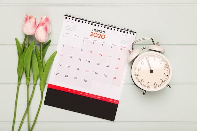 Ramo de tulipanes junto a calendario y reloj Foto gratis