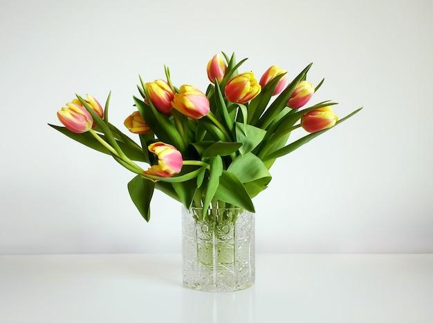 Ramo de tulipanes naranjas en un jarrón bajo las luces sobre un fondo blanco. Foto gratis