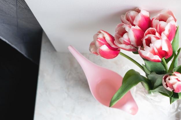 Ramo de tulipanes rosados y regadera en casa vista superior, interior. hermosas flores, estilo de vida. felicitación de vacaciones, vertical Foto Premium