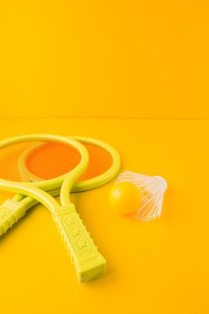 Raqueta de tenis de plástico con pelota y volante contra fondo amarillo Foto gratis