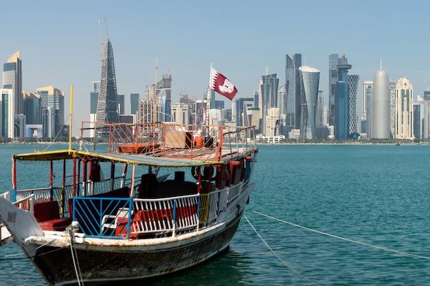 Rascacielos en el centro de la ciudad con agua y primer plano del barco de doha, qatar. Foto Premium