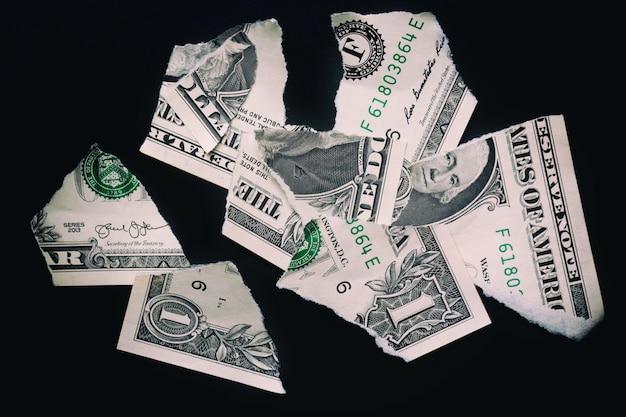 Rasgado rasgado devaluó el billete de banco de un dólar en una superficie negra. Foto Premium