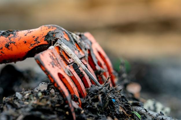Rastrillo anaranjado del primer en la pila de basura plástica sucia en fondo borroso. concepto de contaminación ambiental de playa limpiar la basura en la playa. basura del océano costa contaminada. Foto Premium
