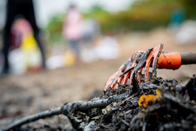 El rastrillo anaranjado del primer en la pila de basura sucia en el fondo borroso del voluntario limpia la playa. concepto de contaminación ambiental de playa ordenando basura en la playa. basura del océano costa contaminada. Foto Premium