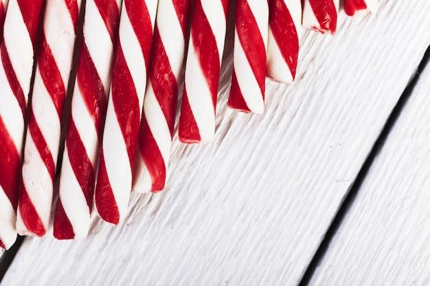 Rayas tubos rojos y blancos en tablero de madera Foto gratis