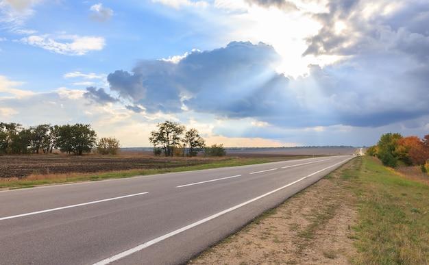 Los rayos del sol atraviesan las nubes y el camino vacío Foto Premium