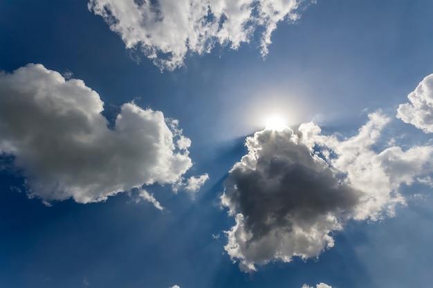 Rayos de sol brillando a través de nubes blancas hinchadas y cielo azul Foto Premium