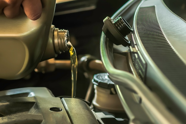 Reabastecimiento de combustible y vertido de aceite rellene el aceite en el motor, el mantenimiento y el rendimiento. Foto Premium