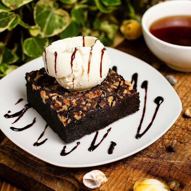 Una rebanada de brownie de chocolate con helado de nuez y vainilla. Foto gratis