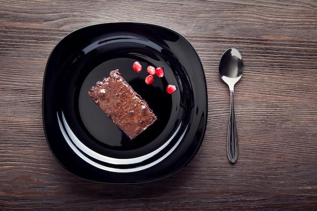 Rebanada de brownie en plato negro sobre una mesa de madera con una cuchara y semillas de granada Foto Premium