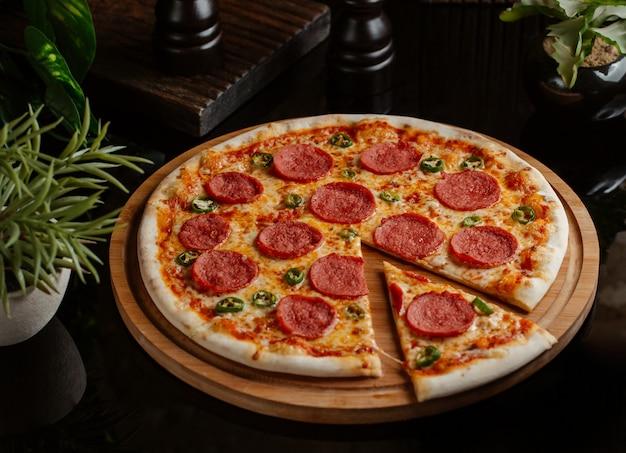 Una rebanada cortada de la clásica pizza de pepperoni con rollos de pimiento verde Foto gratis