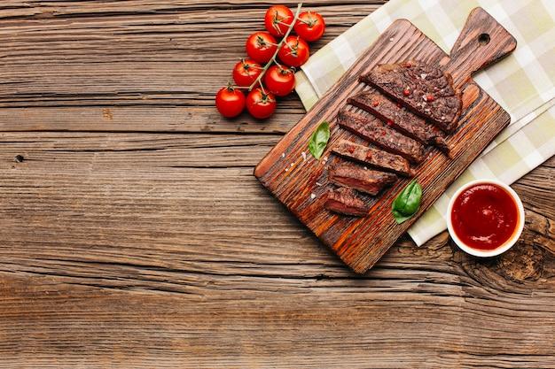 Rebanada de filete a la parrilla en tabla de cortar y tomate sobre fondo de madera Foto gratis