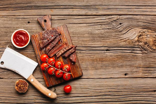 Rebanada de filete a la parrilla y tomate cherry rojo en tabla de cortar sobre mesa de madera Foto gratis