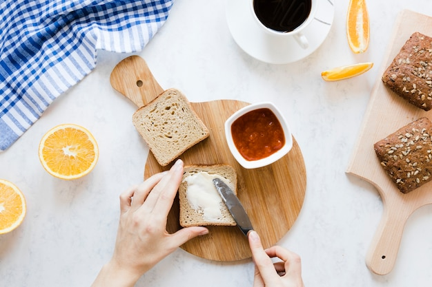 Rebanada de pan con mermelada de mantequilla y café Foto gratis