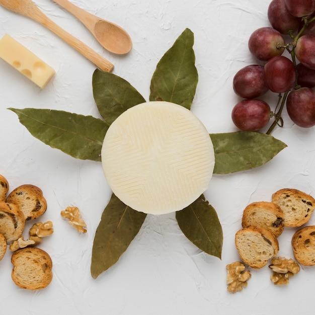 Rebanada de pan nuez; uvas; hojas de laurel y cuchara de madera con queso manchego español. Foto gratis