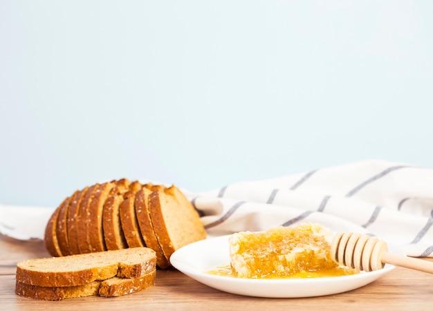 Rebanada de pan y panal para el desayuno en superficie de madera Foto gratis