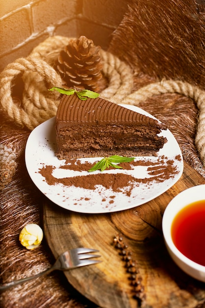 Rebanada de pastel de chocolate y cacao servido con hojas de menta Foto gratis