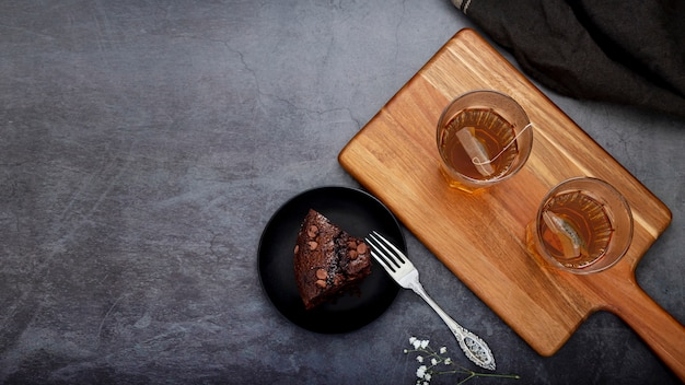 Rebanada de pastel y tazas de té sobre un soporte de madera sobre un fondo gris Foto gratis
