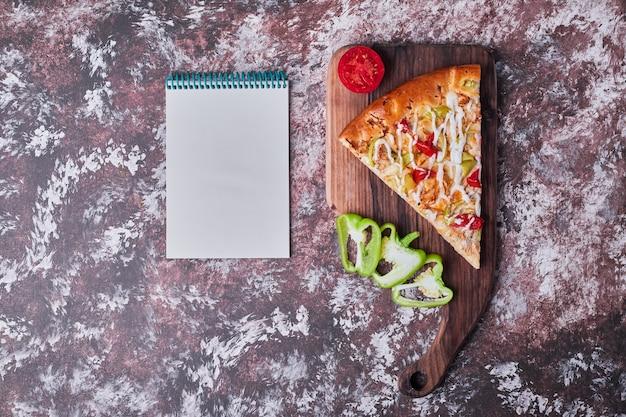 Una rebanada de pizza en una tabla de madera con un libro de recetas a un lado en el mármol. Foto gratis