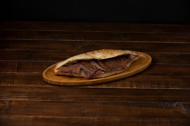 Rebanadas de filete de res en pan en un plato de madera Foto gratis