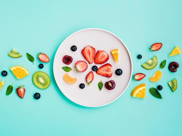 Rebanadas de fruta dulce exótica en un plato blanco sobre fondo turquesa Foto gratis