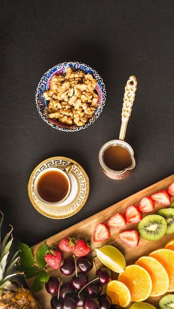 Rebanadas de fruta con té y tazón de nuez fresca en la mesa Foto gratis