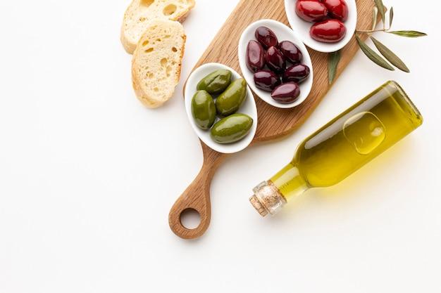 Rebanadas de pan y aceitunas verde rojo púrpura con botella de aceite de oliva Foto gratis