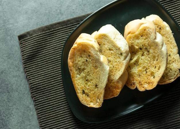 Rebanadas de pan de ajo y hierbas sobre la mesa, sabroso pan con ajo Foto Premium