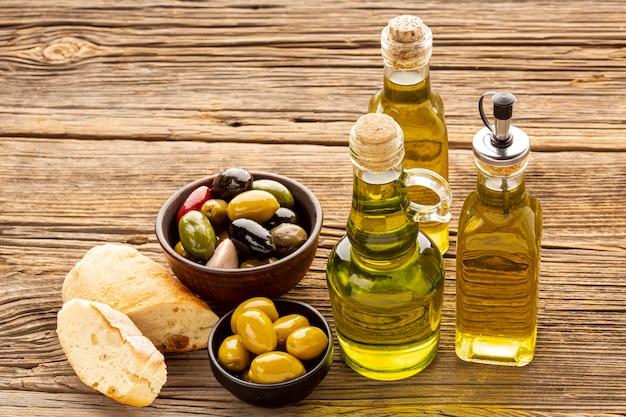Rebanadas de pan de alto ángulo cuencos de oliva y botellas de aceite Foto gratis