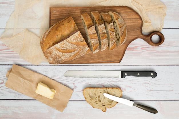 Rebanadas de pan; cuchillo; mantequilla sobre papel y navaja sobre mesa de madera. Foto gratis